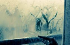 Drawing heart on wet window. Woman drawing heart on wet window Stock Photography