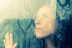 Drawing heart on wet window. Woman drawing heart on wet window Royalty Free Stock Image