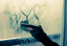 Drawing heart on wet window Royalty Free Stock Photos