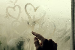 Drawing heart on wet window Stock Photo