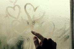 Drawing heart on wet window. Woman drawing heart on wet window Stock Photo