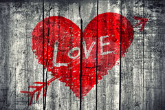 Drawing of a heart with word. Drawing of abstract heart pierced by an arrow with word Love on grunge wooden wall background Stock Photo