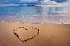 A drawing of a heart on a yellow sand at a beautiful seascape ba Stock Images