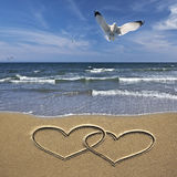 Drawing hearts in the sand Royalty Free Stock Photo