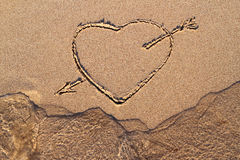 Drawing hearts in the sand and sea wave Royalty Free Stock Photography