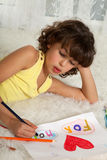 Drawing for her mother. Little girl making a drawing for mother's day stock photography