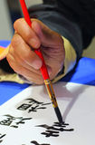 Drawing a hieroglyph. Hand with a brush draws the hieroglyph Royalty Free Stock Photos