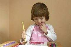Drawing at home. Little, cute, girl drawing with crayons at home Royalty Free Stock Photography