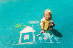 Drawing house with chalk. View from above of beautiful blonde little girl sitting on the playground rubber surface with chalk drawing looking up Royalty Free Stock Images