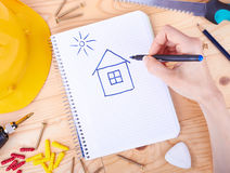 Drawing house and different tools  on a wooden background. Hand drawing a house and different tools  on a wooden background Stock Photography