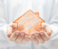 Drawing house in hands. Small orange drawing of a house in hands royalty free stock photography