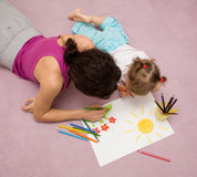 Drawing lesson. Beautiful mother draws with a small daughter lying on a floor Stock Image
