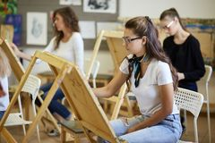 Drawing lesson in the art studio. Tree charming young girls paint pictures sitting at the easels royalty free stock photos