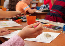 Drawing lesson in kindergarten. Paints, pencils and paper for the education of children drawing on the table royalty free stock images