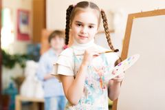 Drawing lesson. Portrait of a girl standing next to his easel, a drawing lesson Stock Photos