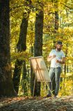 Drawing from life. Painter artist forest. Art concept. Painting in nature. Start new picture. Painter with easel and. Canvas. Bearded man painter looking for royalty free stock photography