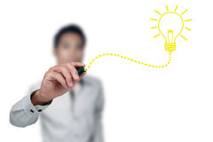 Drawing light bulb. Hand with a pen drawing light bulb Royalty Free Stock Photography