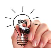 Drawing a light bulb. Female hand drawing a light bulb, isolated on white Royalty Free Stock Photos