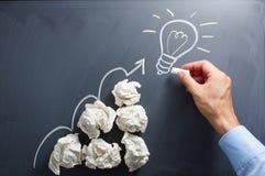 Drawing light bulb on blackboard. Many paper balls. Royalty Free Stock Image