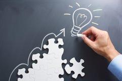 Drawing light bulb on blackboard. Steps shaped jigsaw puzzle. Stock Photo