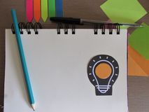 New Idea Concept. Drawing of a light bulb on notebook sheet with pen and colorful papers. stock images