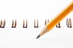 Drawing the line. Close up shot of a sharp yellow pencil drawing a straight line on a white paper notebook Stock Image