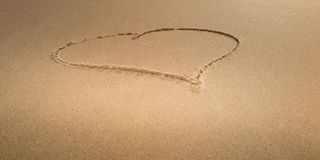 Drawing of love heart as symbol on a yellow sand at sea stock photo