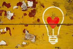 Drawing love symbol in light bulb on old wooden wall Stock Photos
