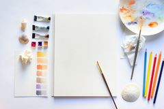 Drawing mockup with blank textured paper and watercolors. Coloring pencils, seashells, top view flat lay template Stock Photo