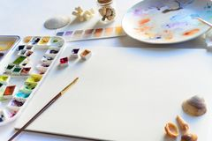Drawing mockup with blank textured paper and watercolors. Palette, seashells, top view flat lay template Stock Images