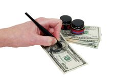 Drawing money. Calligraphy pen that is dipped into ink and drawn across paper to make flourished embellishments drawing money-Path included Royalty Free Stock Images
