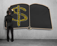 Drawing money symbol on book shape blackboard. On concrete wall Royalty Free Stock Photos