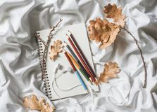 Drawing notepad, colored pencils, dried leaves of oak, headphones in bed, top view. Weekend cozy leisure concept. Flat lay Royalty Free Stock Image