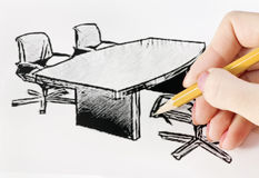 Drawing office furniture. Hand with a pencil drawing arrangement of furniture for the office stock photo