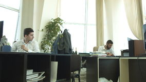 Drawing in the office. A young man throws a piece of paper at his colleague and laughs. HD stock footage