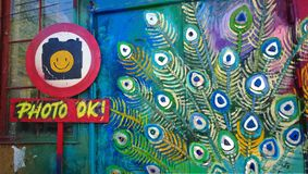 Drawing on one of the buildings in the free city of Christiania with the sign permission to take a photo. A bright wall at the ent. Rance to the art store royalty free stock image