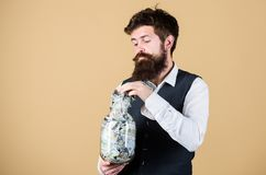 Drawing out money for running startup business. Startup concept. Businessman taking money out of glass jar to cover. Startup costs. Bearded man investing money stock photo