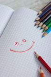 Color pensils and drawing pad. Drawing pad with color pensils. Red and orange pensils in front. Drawing of smile in the pad stock images