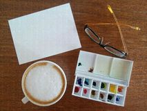 Drawing paper with watercolor plate and hot coffee lay on the table Stock Images