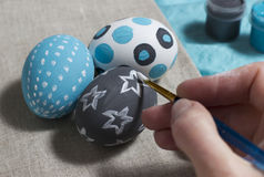 Drawing of patterns on Easter eggs. Life symbol on Easter holiday. The tradition to paint eggs in different colors and patterns. White gouache drawing a star on Stock Photos