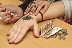 Drawing patterns by henna on the hands Stock Images