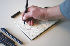 Drawing in pen and ink. Shot of a person drawing in small book with pen and ink royalty free illustration