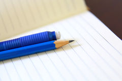 Drawing pencil and eraser over a white notebook Royalty Free Stock Photos