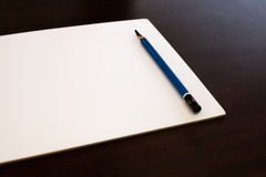 Drawing Pencil and white paper on dark brown background. Stock Image