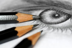 Drawing pencils. Close up of graphite drawing pencils laying on paper with eye Royalty Free Stock Photos