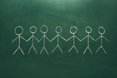 Drawing of people holding hands together. On chalkboard. Unity concept stock photography