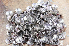 Drawing pins. Or thumb tacks on rustic wooden background Royalty Free Stock Image