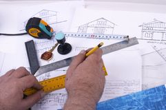 Drawing a plan. A draughtsman / architect's hands drawing something into his design Stock Photography