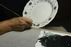 Drawing porcelain. A process of traditional chinese handmade porcelain from Germany. Human hand of an art painter is drawing the porcelain as first step of Royalty Free Stock Photos