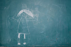 Drawing of princess on chalkboard by child stock image